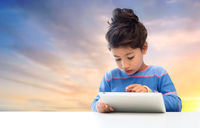 little girl with tablet pc over evening sky