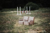 conceptual photo a wooden armchair with a gray handmade seat is standing in the horse training court