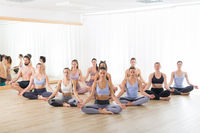 Group of young sporty attractive people in yoga studio, practicing yoga lesson with instructor, sitting on floor in Siddhasana, easy seated yoga pose. Healthy active lifestyle, working out in gym