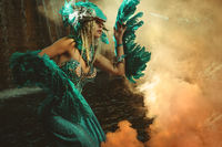 Fantasy scene, Beautiful blonde woman in fancy dress and blue angel wings on arms