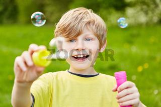 Junge macht Seifenblasen und schaut staunend