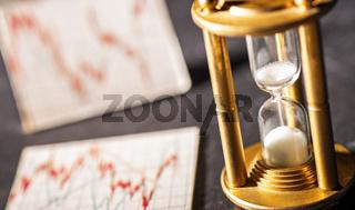Sanduhr und Aktienkurse Konzept Geldanlage