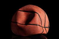 Deflated and rumpled old basketball ball