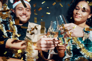 Multiethnic friends toasting with champagne celebrating Christmas party