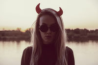 Deadlly serious female wearing sunglasses and Devils horns