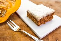 Homemade cake made of coconut and pumpkin over a wood background