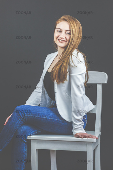 Long-haired, woman, 20-30, casual, with jeans and blazer (jacket), sitting on a chair.