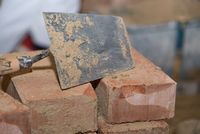 Trowel and small bricks - close-up of smoothing trowel