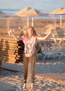 Young girl, tween age, wearing casual summer clothing, throwing sand in the air on the beach