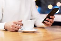 Handsome young caucasian man sitting at cafe using mobile phone and having coffee. Caucasian male with cup of coffee and reading text message on his smart phone.