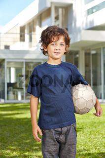 Kind mit Fußball im Garten