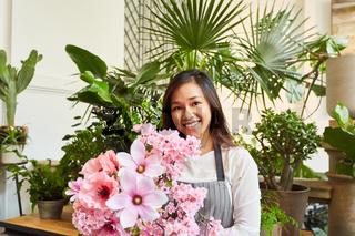 Junge Floristin mit einem großen Blumenstrauß