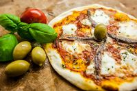 Original Italian Pizza Napoletana on brown wood background. Pizza with anchovies and capers close up
