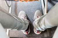 Male passenger with lack of leg space on long commercial airplane flight. Focus on casual sporty sneakers