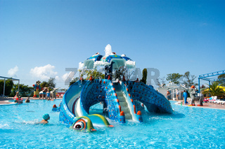 Aqualoo Waterpark - view of the dragon slide in the children's pool. In the background, an elephant fountain blows a stream of water from a trunk