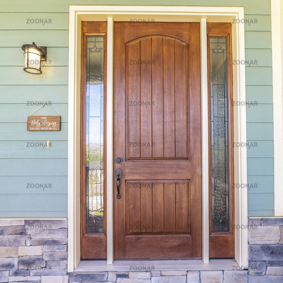 Square frame Front view of a home with green wall and brown wood door flanked by sidelights