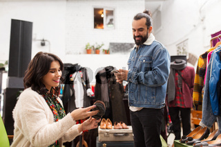 couple choosing footwear at vintage clothing store