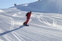 Snowboarder in red downhill on snowy ski slope