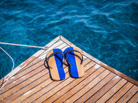 Flip flops on pier above clear blue water