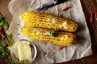 Top view of kitchen table with grilled sweet corn cob under melting butter and greens on baking paper