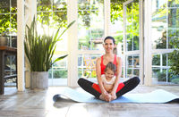 Young brunette woman with little daughter in a sporty uniform doing yoga