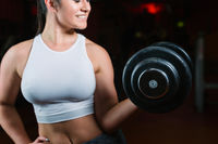 Woman with dumbbells, black background