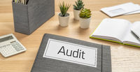 A folder on a desk with the label Audit