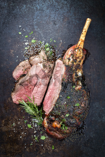 Traditional barbecue leg of lamb sliced with spice and herb as top view on a metal sheet