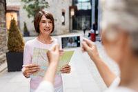 senior women with city map on street in tallinn