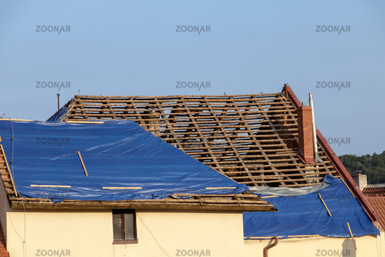 The tarp covers the roof of the old house in the reconstruction.