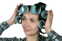 fifty-year-old woman holding hair curlers on her hair