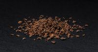 Grated chocolate. Heap of ground chocolate isolated on black background, closeup