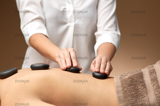 close up of woman having hot stone massage at spa