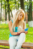 Beautiful young blonde woman in blue t-shirt sits on bench and writes in a notebook