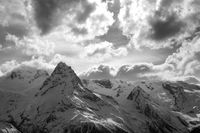 Black and white view on high evening mountains in sunlit clouds
