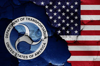 flags of Department of Transportation and USA painted on cracked wall
