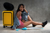 Portrait of smiling young Asian woman with luggage isolated over concrete wall background