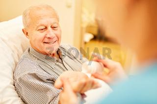 Pflegekraft gibt Senior Mann Tabletten