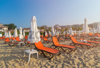 Red chairs and umbrellas on a beautiful beach at sunrise in Sunny Beach on the Black Sea coast of Bulgaria