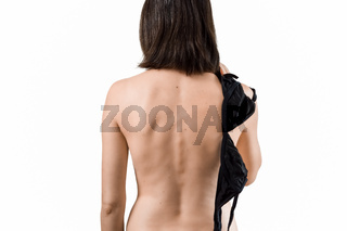 Beautiful girl standing with a bare back, holding a black bra in her hand
