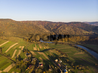 Carpathian Mountains, Ukraine. Aerial Drone View of autumn mountains with forests and river, meadows and hills in sunset soft light