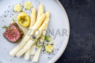 Modern German barbecue dry aged sliced fillet steak with white asparagus and roast potatoes in butter sauce as top view on a plate with copy space right