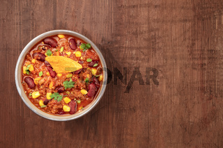 Chili con carne, shot from above on a dark rustic wooden background with a place for text