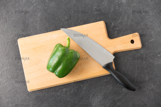 green pepper and kitchen knife on cutting board