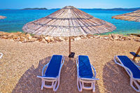 Idyllic turquoise beach parasol and deck chair in Orebic