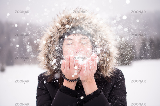young woman blowing snow on snowy day