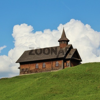 Beautiful old timber chapel on a green hill in Stoos, Switzerland.