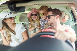 Familie mit zwei Kindern beim Auto fahren