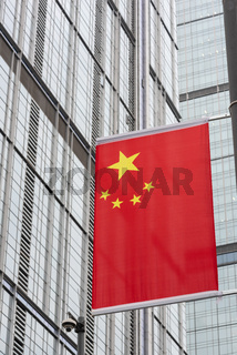 chinese flag against skyscraper facade