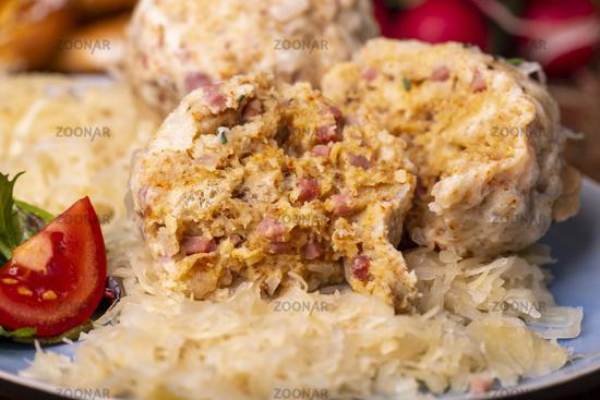 zwei Speckknödel mit Sauerkraut auf Holz